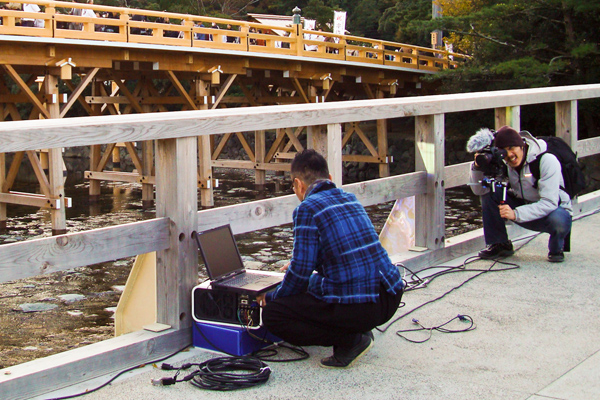 Peter H. Chang films Akira Hasegawa setting up projectors for D-K