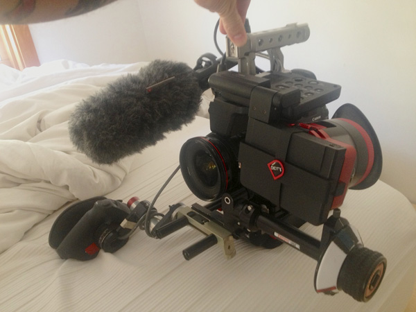 Jake's current C300 handheld rig, with a Movcam top handle. The Zacuto recoil lite puts the camera right on his shoulder for better weight distribution. The extended follow focus sits out past the LCD screen, which has the Diety, Miro Loupe. On the front is the custom handgrip offset made by Abel Cinetech. His shotgun is mounted off to the side, so the camera doesn't get too tall. Photo by Jake Burghart