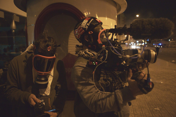 Jake and Brendan taking cover in the streets of Cairo, shooting handheld with a 70-200mm Photo: Jerry Ricciotti