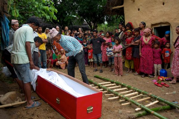 The relatives of Ganesh Bishwakarma, prepare his body for cremation in his village of Dharana, Nepal