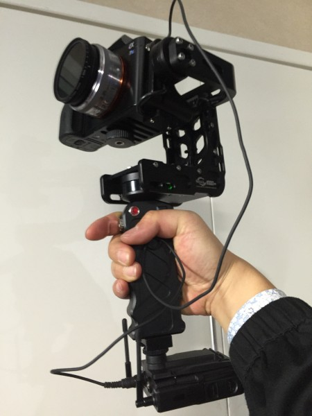 A Sony UWP-D wireless mic attached via a cold shoe to the base of the Nebula handgrip