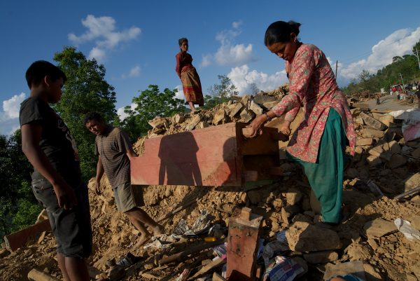 Dil Bahadur Shrestha dig out their belongings from what remains of their home in Harredada, Sindhupalchowk district, Nepal.
